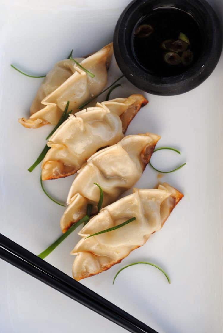 Asian pot stickers are delicious Asian dumplings filled with spinach, green onions, ginger, and pork. They're a tasty appetizer, or serve them with a side salad for a light meal. \\ Get the recipe on PassTheSushi.com