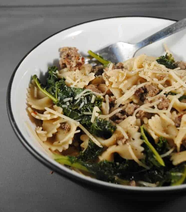 White bowl with italian sausage, farfalla pasta and kale