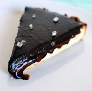 Salted caramel chocolate tart tastes amazingly like a Twix candy bar. Salted caramel and chocolate inside of a tender shortbread crust. Get the dessert recipe from PassTheSushi.com