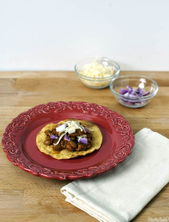 Pork tinga is a Mexican tostada dish made with flavorful shredded pork. It's an easy to prepare, hearty, and filling comfort food dinner. \\ PassTheSushi.com