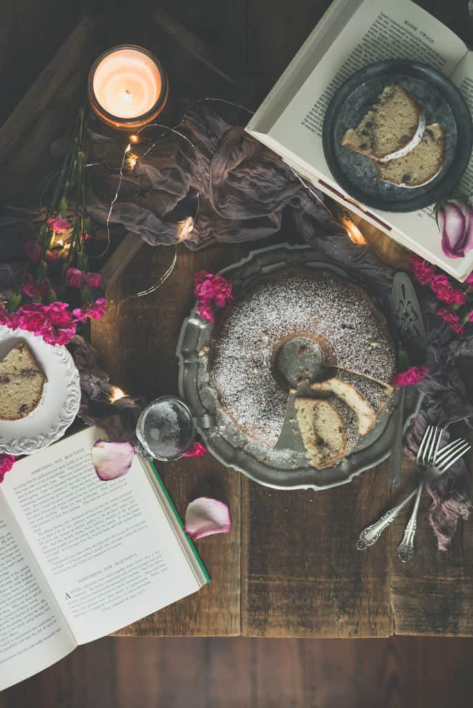 Coffee Cake dusted in powdered sugar seen from above with an open book, flower petals and forks in the scene | Kita Roberts PassTheSushi.com