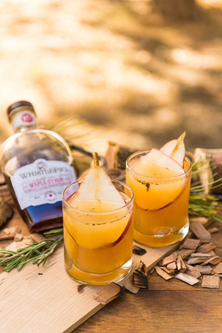 2 glasses of pear white wine sangria with pear slices in each on a wooden board