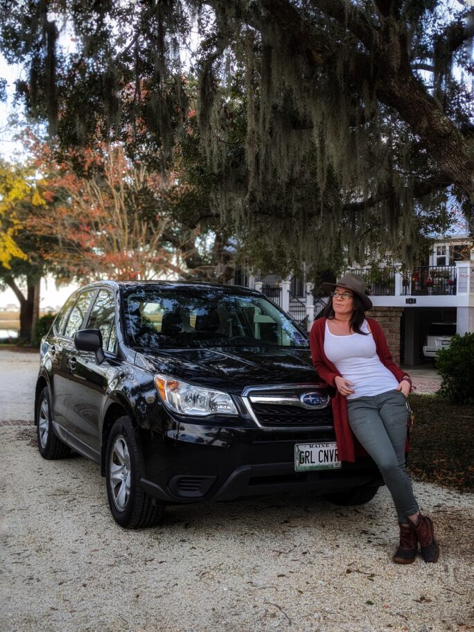Woman leaning on black subaru forester