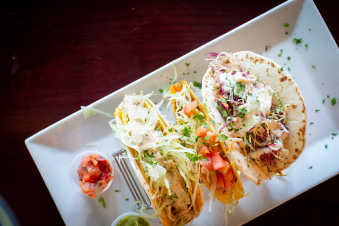 Taco Tuesday - three different tacos on a white plate at Mauras kitchen