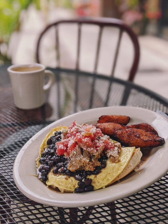 a Cuban breakfast with hearty pulled pork, beans, eggs, toast, and of course fried plantains at Herencia Cafe