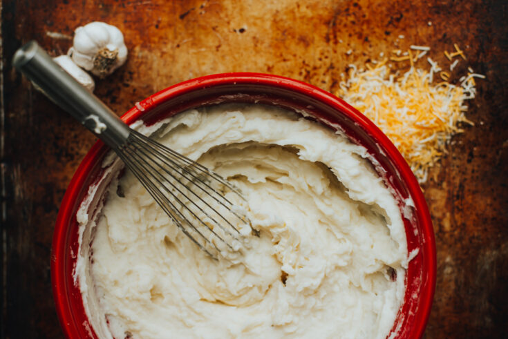 Creamy mashed potatoes in a red bowl with garlic and cheese on the surface around the bowl.